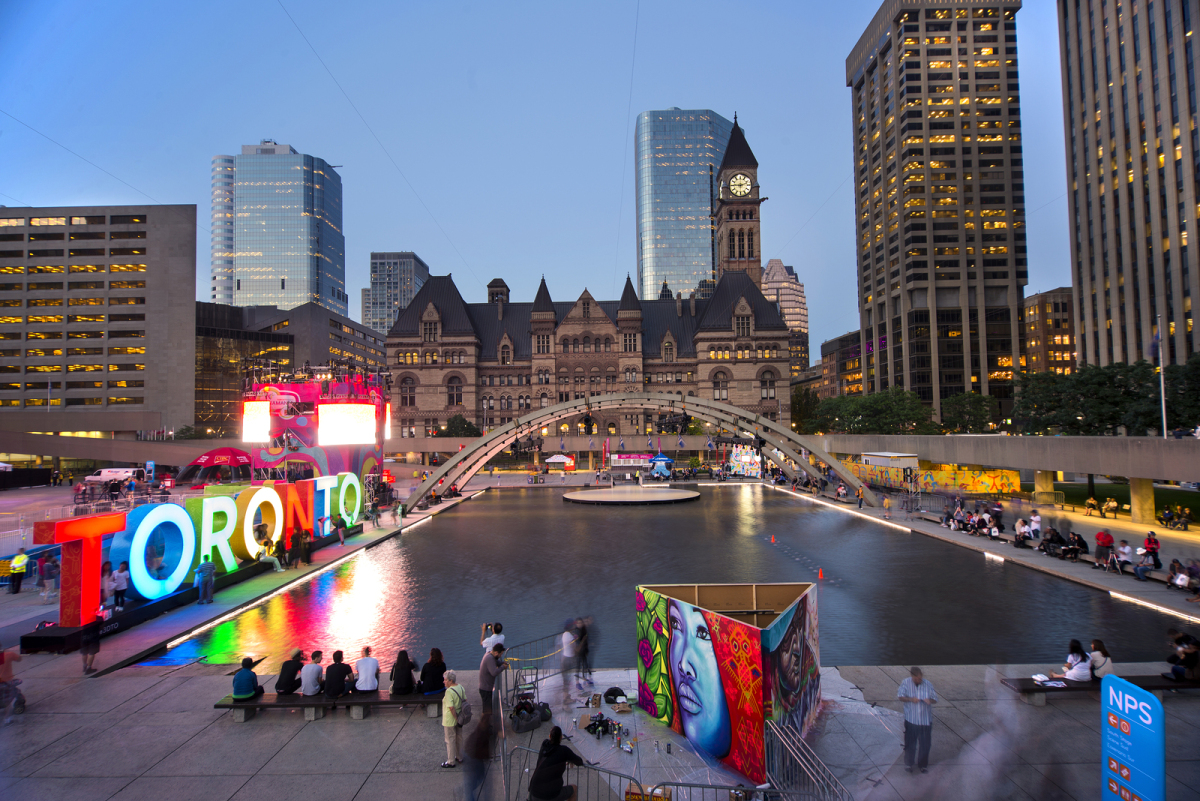TORONTO,CANADA-JULY 9,2015: Panoramic view of the new Toronto sign in Nathan Phillips Square, host of PanaMania, a constant party celebrating the PanAm games. Old City Hall in the back.